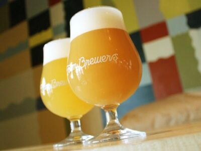 two hazy IPAs in craft beer glasses