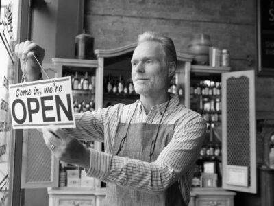 "coffee shop clerk flipping the ""We're Open"" sign on the front door"