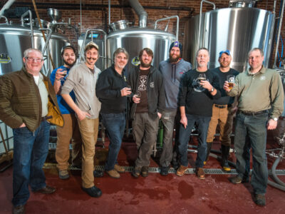 Group of white brewers in front of beer tanks